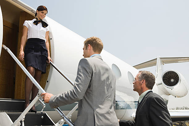 stewardess and businessmen boarding jet - getting on stock photos and pictures