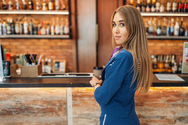 Stewardess at the bar counter in airport cafe stock photo