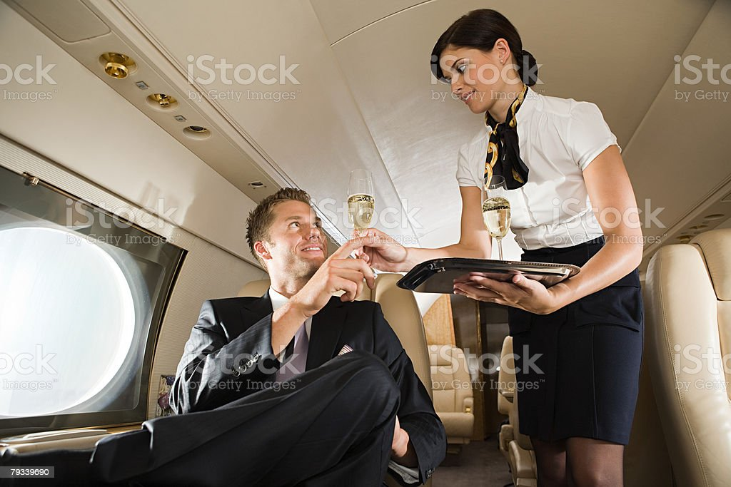 Stewardess handing champagne to man stock photo