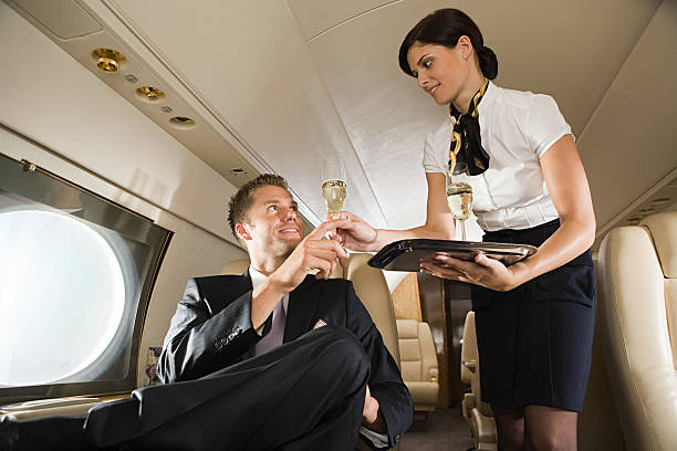 Stewardess handing champagne to man  cabin crew stock pictures, royalty-free photos & images