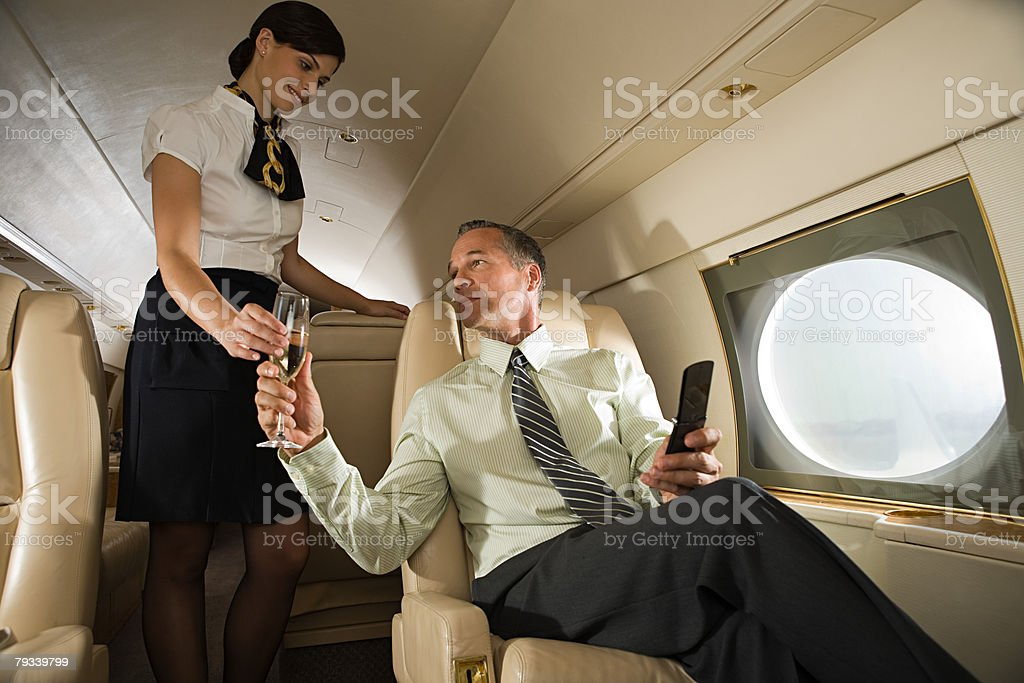 Stewardess handing champagne to man royalty-free 스톡 사진