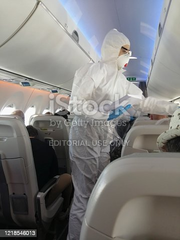 Stewardess in a white overalls and mask in the cabin serves passengers. Coronavirus pandemic time.Amsterdam / Netherlands - March 26 2020: Stewardess in a white overalls and mask in the cabin serves passengers. Coronavirus pandemic time. Amsterdam - Riga flight.