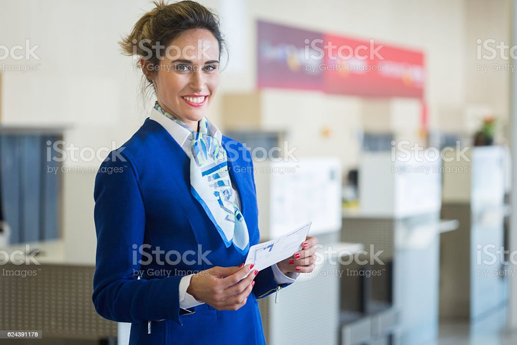 Stewardess looking at camera and holding a boarding pass stock photo