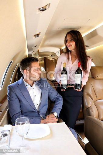 istock Stewardess of business jet offering red and white wine 539980862