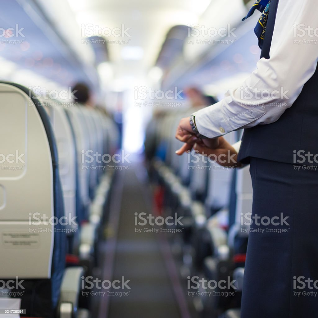 Stewardess on the airplane. Interior of airplane with passengers on seats and stewardess in uniform waiting at the aisle.  Air Stewardess Stock Photo