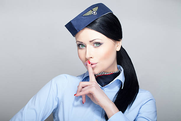 Stewardess quieting down Attractive young woman stewardess flight attendant with green eyes quieting down air stewardess stock pictures, royalty-free photos & images