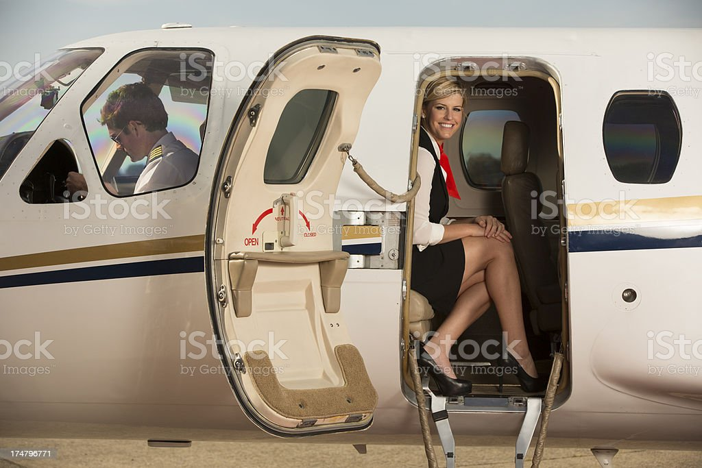 Stewardess sitting in a jet, looking thru open door stock photo