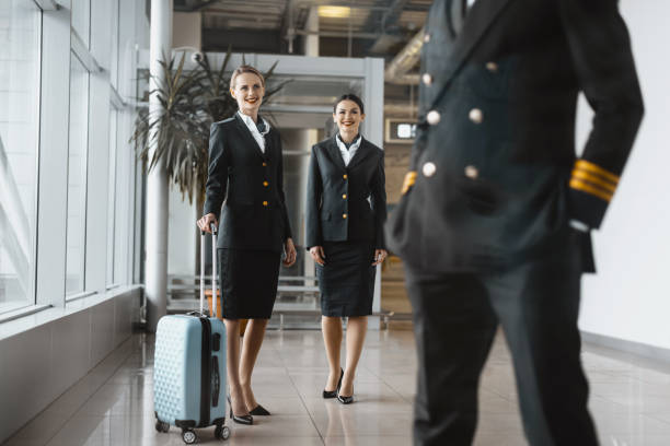 stewardesses looking at pilot at airport lobby before flight stewardesses looking at pilot at airport lobby before flight cabin crew stock pictures, royalty-free photos & images
