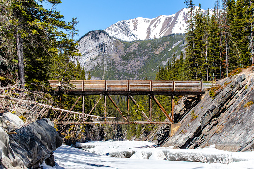 The bridge over a frozen Stewart canyon with mount Astley in the background
