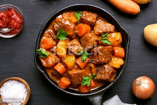 Beef meat stewed with potatoes and carrots in cast iron pan on dark background, top view