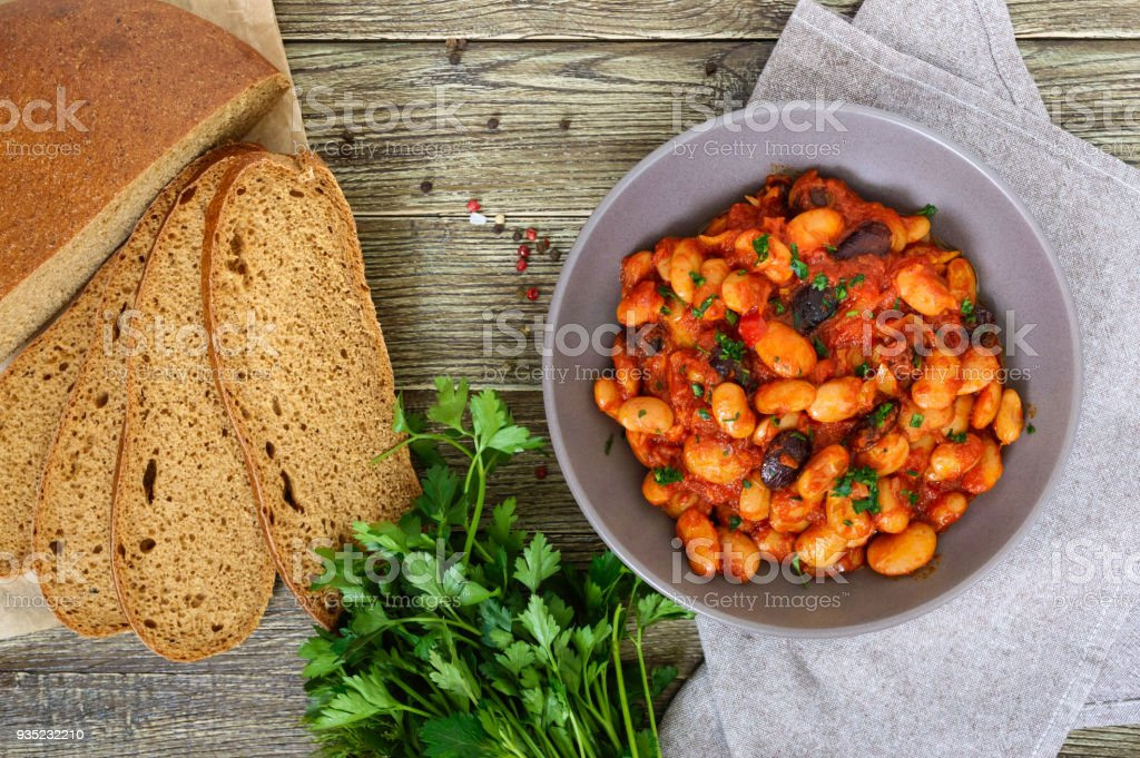 Stewed broad beans in tomato sauce with herbs and spices close-up, slices of rye bread on the wooden table. Lenten menu. Vegan dish. The top view. stock photo