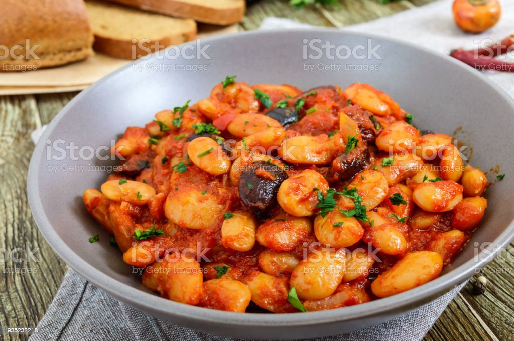 Stewed broad beans in tomato sauce with herbs and spices close-up, slices of rye bread on the wooden table. Lenten menu. Vegan dish. stock photo