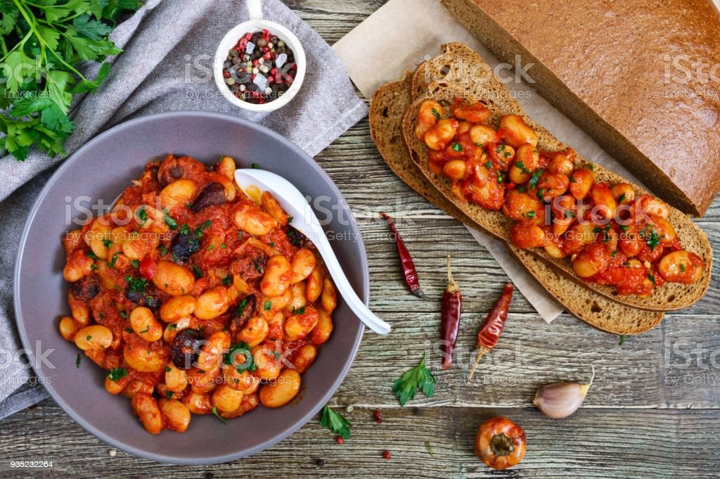 Stewed broad beans in tomato sauce with herbs and spices closeup. Slices of rye bread with beans on the wooden table. Lenten menu. Vegan dish. The top view. stock photo