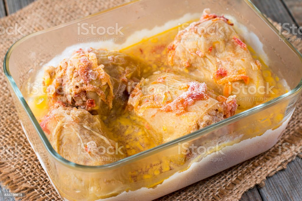 Stewed frozen stuffed pepper in a glass container. Frozen food stock photo