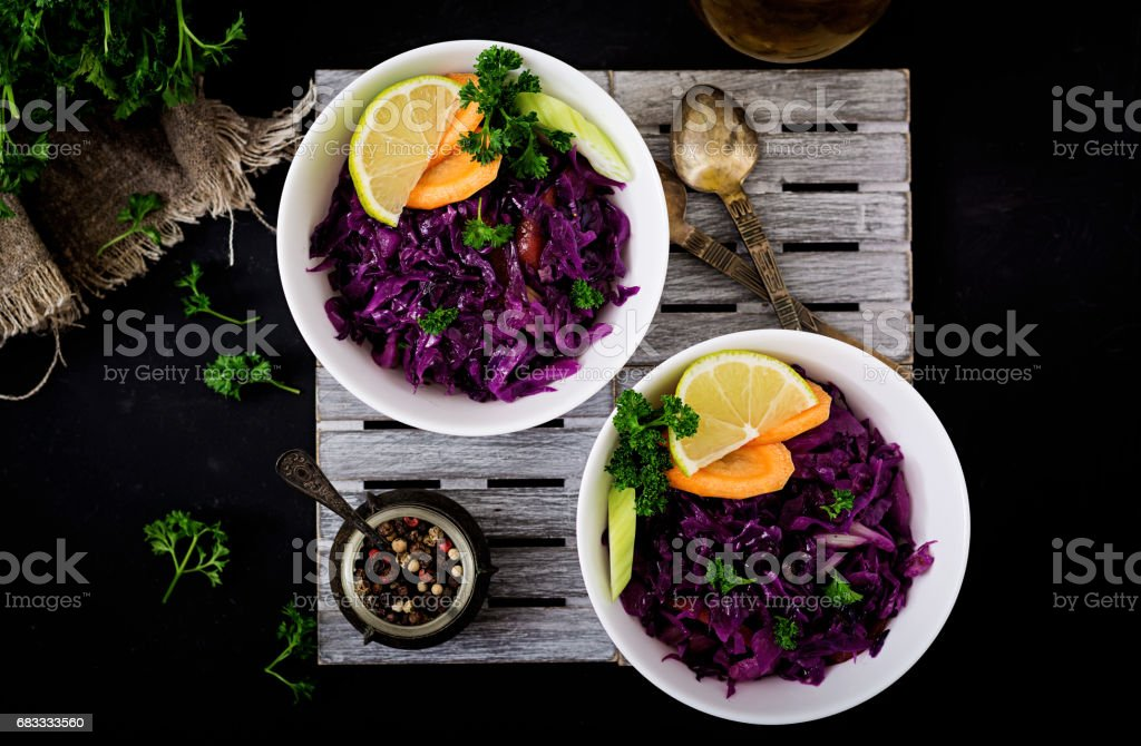 Stewed red cabbage with carrots and celery in a white bowl on a black background. Flat lay. Top view royalty-free stock photo