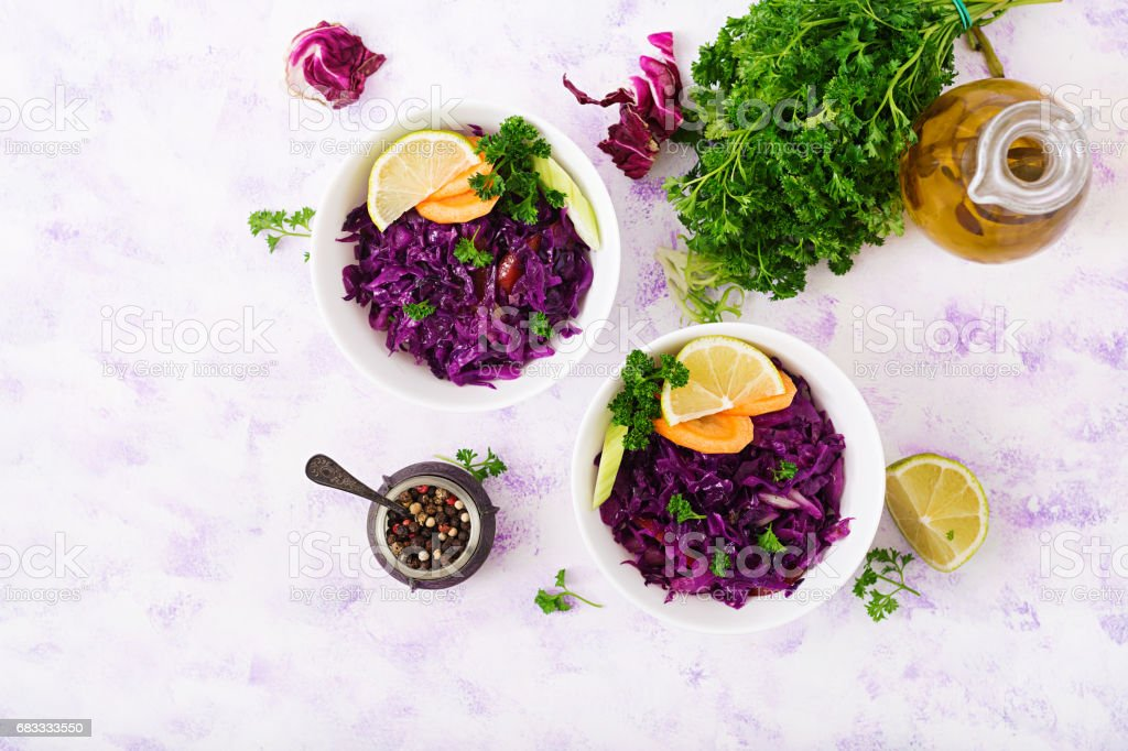 Stewed red cabbage with carrots and celery in a white bowl on a light  background. Flat lay. Top view royalty-free stock photo