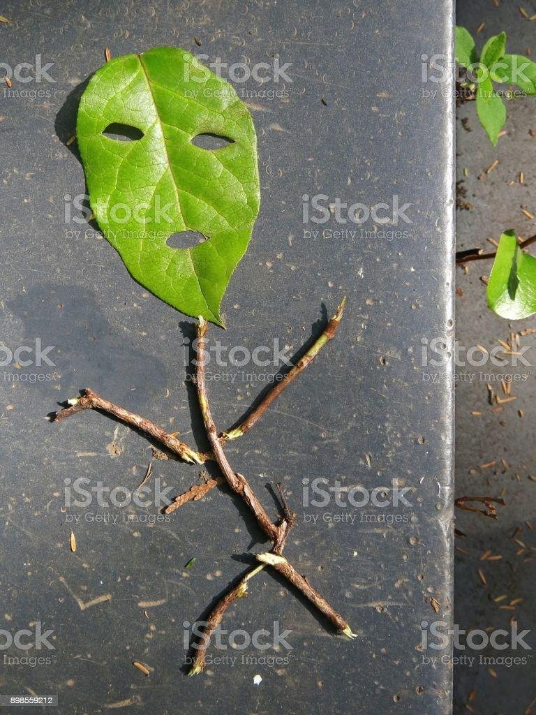 Personne de Stick Figure à l'aide de bâtons et feuille verte - Photo