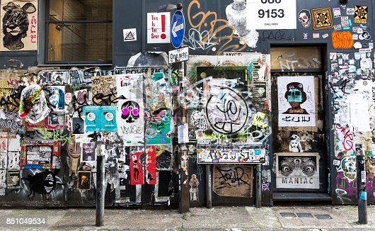 London, UK - August 19, 2017: External wall of a building filled with posters and stickers. Sticker art is frequent form of street art in Hackney, East London.
