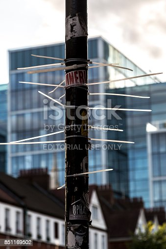 London, UK - August 19, 2017: A street pole tied with plastic bands displayed as a form of sticker street art in Hackney, London.