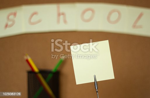 990092558 istock photo Stickers and colored pencils on a blurred background of a cork board with an inscription