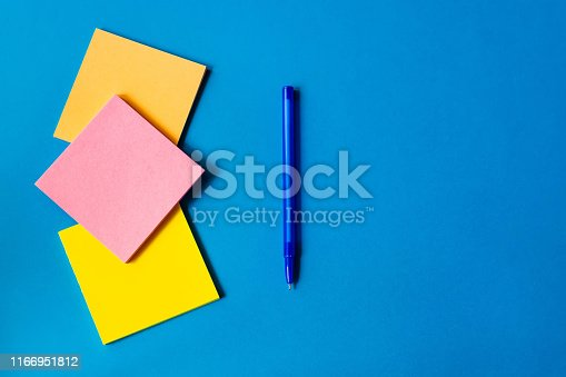 istock stickers for notes and pen lie on a blue background. 1166951812