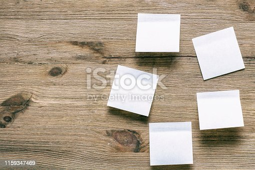 istock Stickers on a wooden background. Piece of paper on wooden table. 1159347469