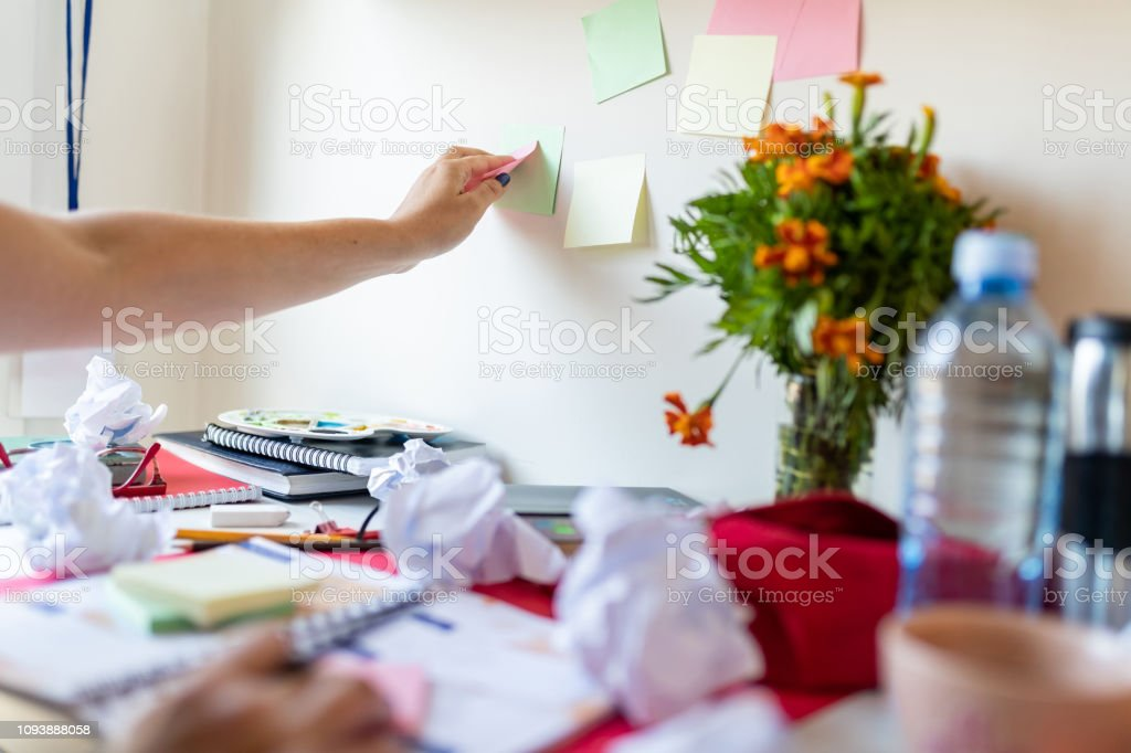 Female hand sticking adhesive notes on the wall above messy desk full...