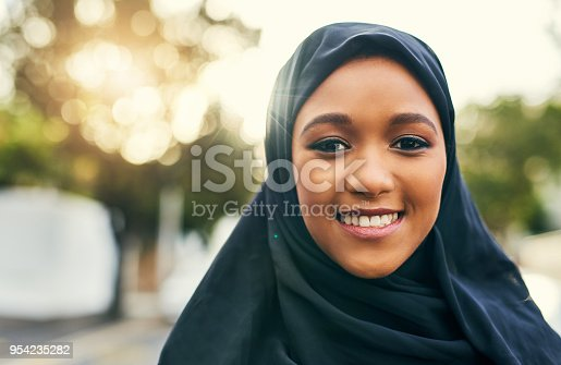 Portrait of a cheerful young woman standing alone and smiling to the camera  outside during the day