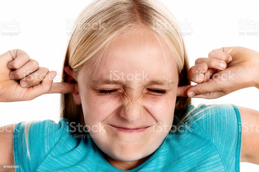 Sticking her fingers in her ears, little girl hates noise stock photo