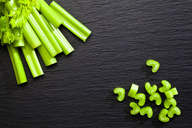 Sticks and chopped celery on dark background stock photo