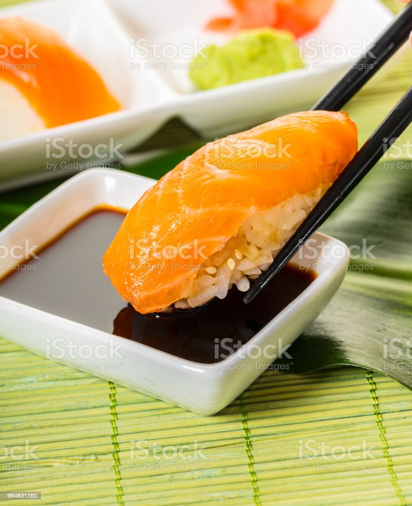 sticks keep sushi with salmon in soy sauce royalty-free stock photo