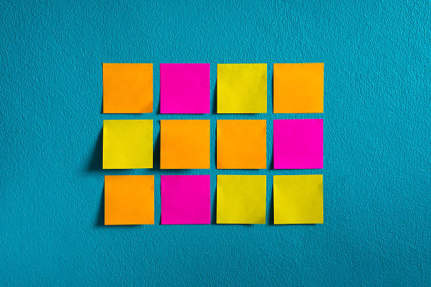 sticks note paper on wall - adhesive note stock photos and pictures