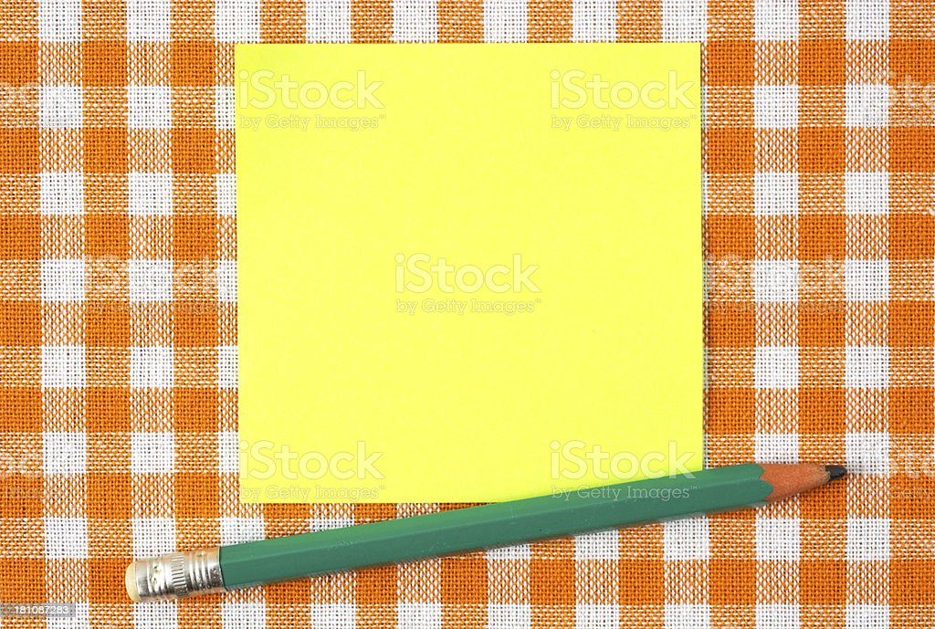 Sticky and pencil on orange tablecloth royalty-free stock photo