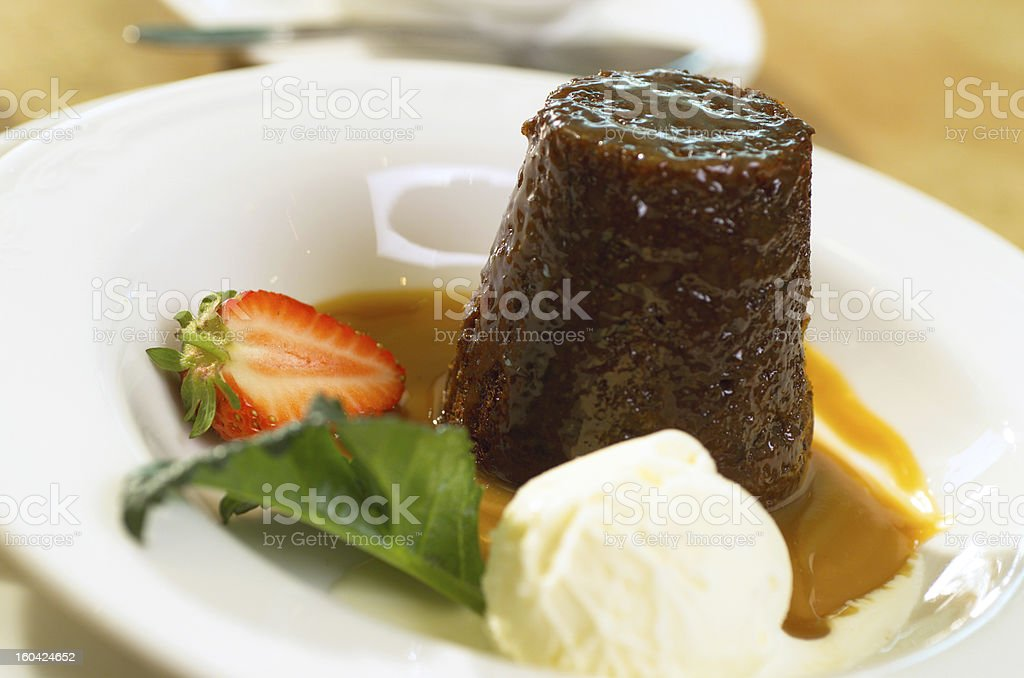 Sticky date pudding with ice cream and a strawberry stock photo