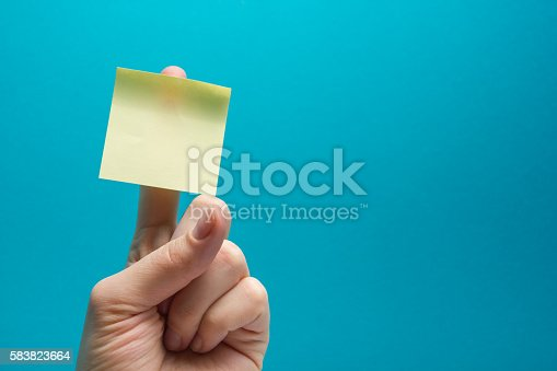 istock Sticky note, finger up of thumb, yellow reminder on blue 583823664