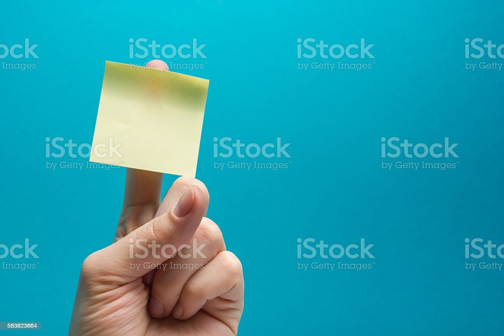 Sticky note, finger up of thumb, yellow reminder on blue - foto stock