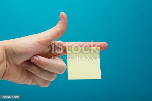istock Sticky note, finger up of thumb, yellow reminder on blue 586374886