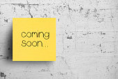 istock Sticky note on concrete wall, Coming soon 1127669251