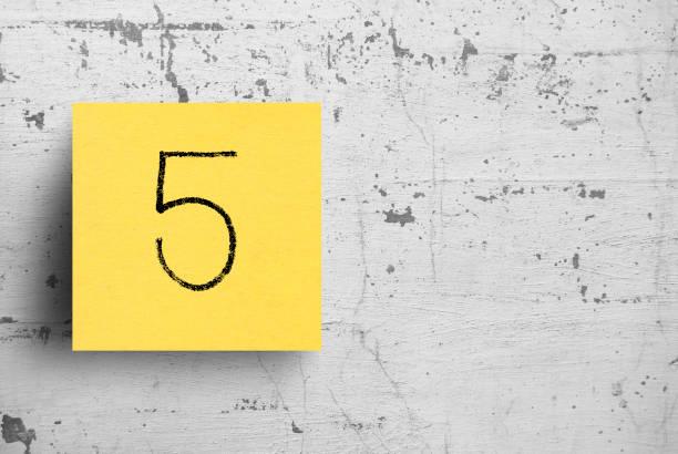 sticky note on concrete wall, number 5 - numero 5 foto e immagini stock
