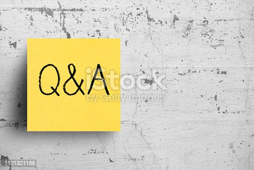 istock Sticky note on concrete wall, Questions, Answers 1131321155