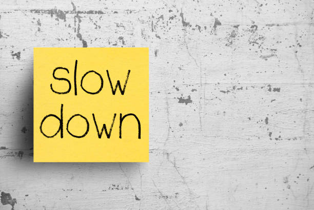 Sticky note on concrete wall, Slow down Sticky note on concrete wall, Slow down slow motion stock pictures, royalty-free photos & images