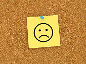 Sticky Note on Corkboard with Sad Emoticon - 3D Rendering