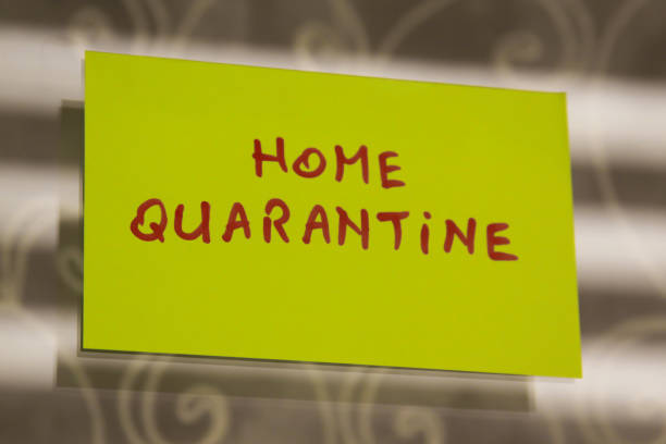Sticky note on window with Home Quarantine writing text message stock photo