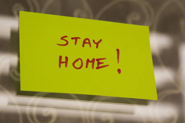 Sticky note on window with Stay Home writing text message stock photo