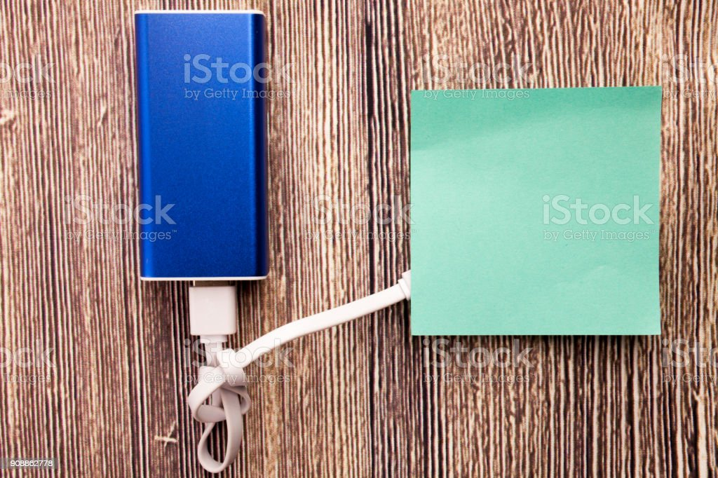 sticky note paper charging with energy bank. Depth of field on Power bank stock photo