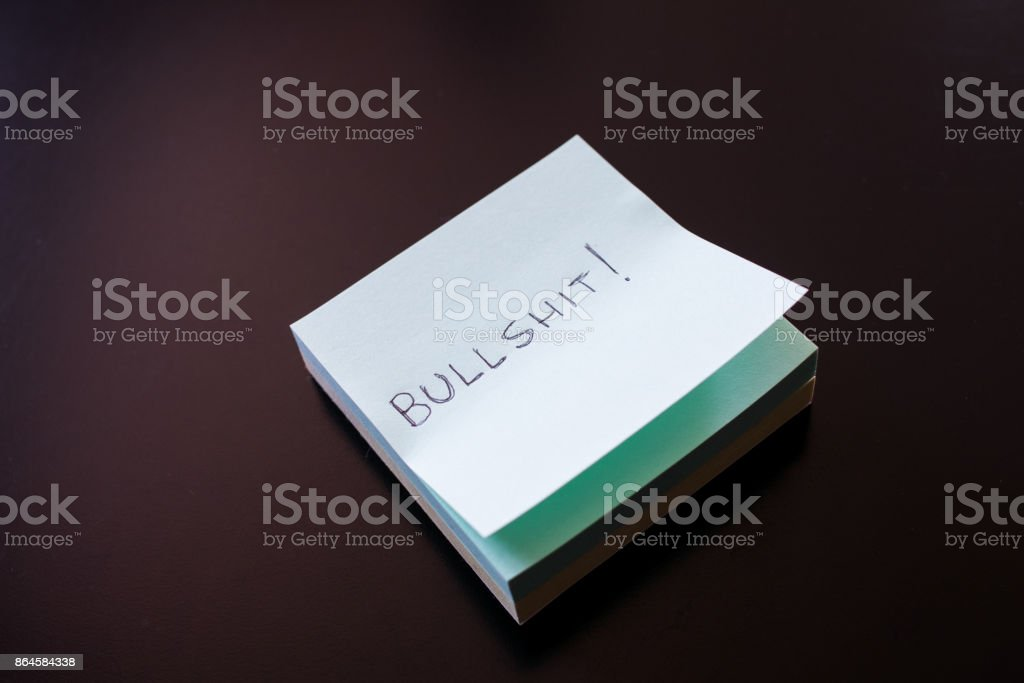 Sticky note with bullshit written on first paper on black background with light on left. stock photo
