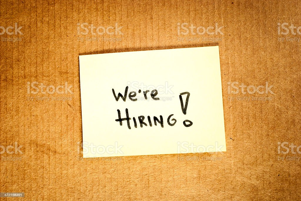 Sticky note with 'We are hiring' message over brown cardboard stock photo