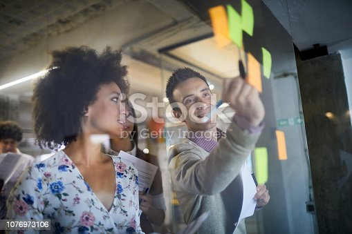 Close up of a group of designers putting up sticky notes in their office