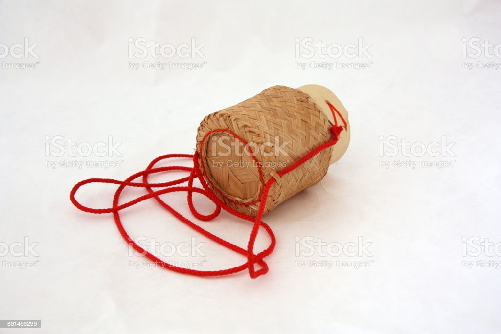 Sticky rice basket with red hanging string on white background. stock photo