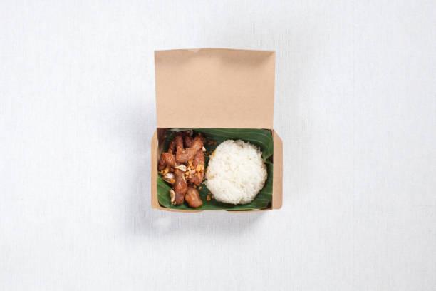 Klebriger Reis mit gebratenem Schweinefleisch in eine braune Papierkiste gelegt, auf eine weiße Tischdecke, Lebensmittel-Box, Thai-Lebensmittel. – Foto